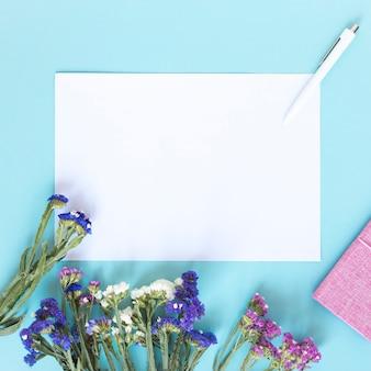Hoja de papel en blanco; pluma y manojo de coloridas flores sobre fondo azul