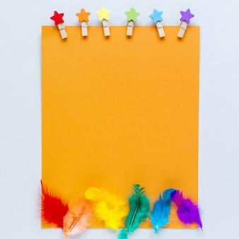 Hoja de papel en blanco con plumas de arcoiris