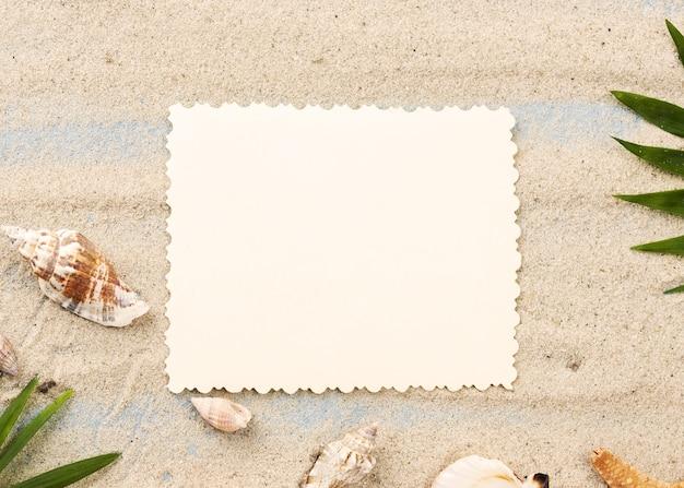 Hoja de papel en blanco sobre arena