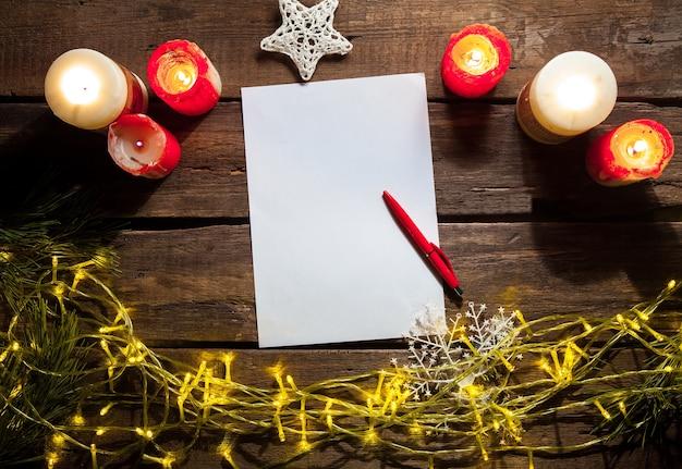 La hoja de papel en blanco sobre la mesa de madera con un bolígrafo y adornos navideños.