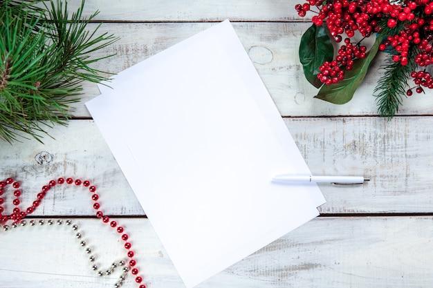 Hoja de papel en blanco sobre la mesa de madera con un bolígrafo y adornos navideños
