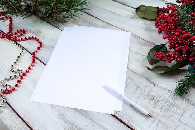 La hoja de papel en blanco sobre la mesa de madera con un bolígrafo