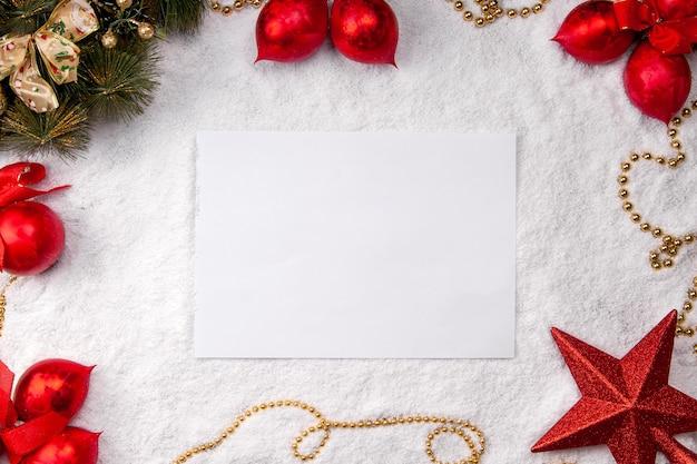 Hoja de papel blanco sobre nieve fondo de navidad vista superior maqueta