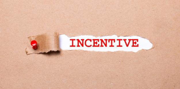Una hoja de papel blanco con el texto incentivo yace sobre virutas blancas sobre un fondo oscuro.