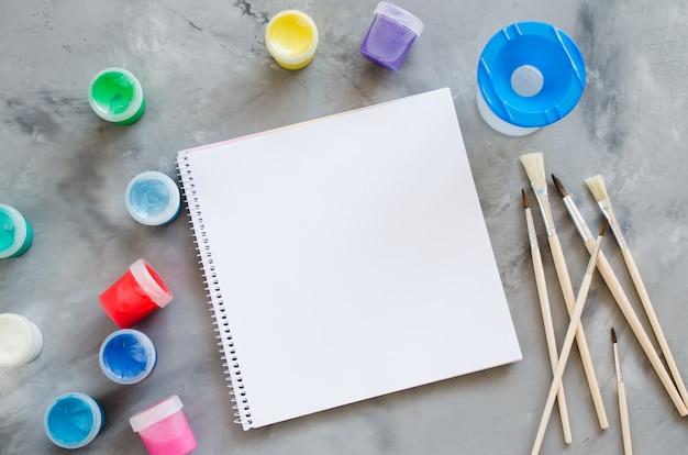 Hoja de papel blanco vacía, pinceles y pinturas. maqueta para dibujar.