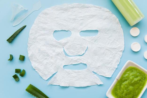 Hoja de papel de cara blanca con aloevera sobre fondo azul