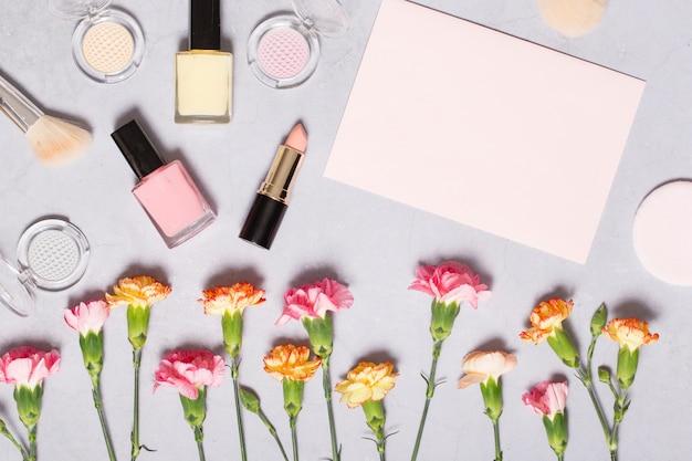 Hoja de papel cerca de cosméticos y claveles