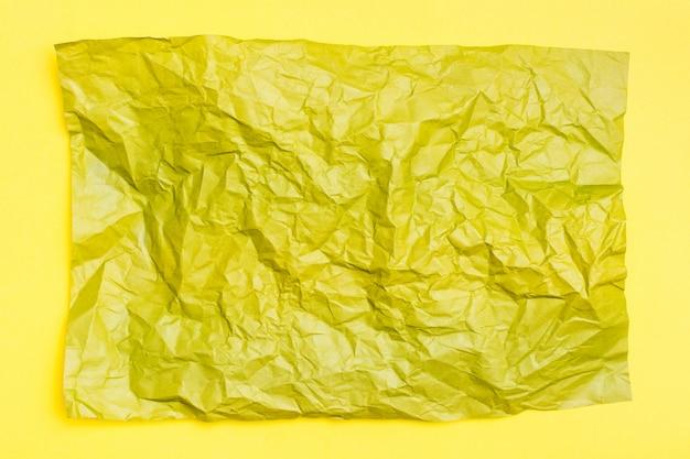 Hoja de papel de color amarillo arrugado en blanco sobre un fondo de cartón amarillo. fondo multicolor texturizado. vista superior. copia espacio
