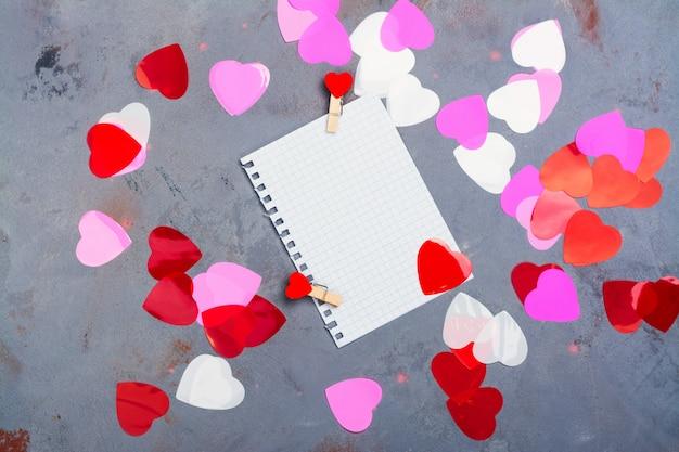 Hoja de papel de cuaderno y corazones decorativos