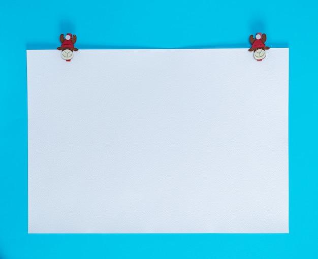 Hoja de papel cuadrada blanca sobre un fondo azul