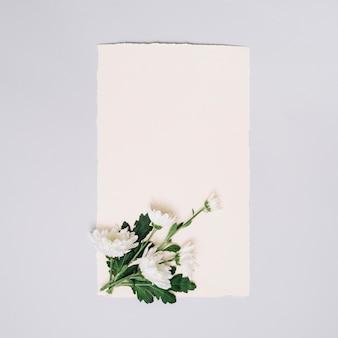Hoja de papel con flores pequeñas en mesa blanca