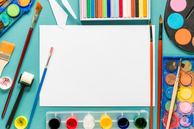 Hoja de papel y herramientas de pintura de artistas en el escritorio
