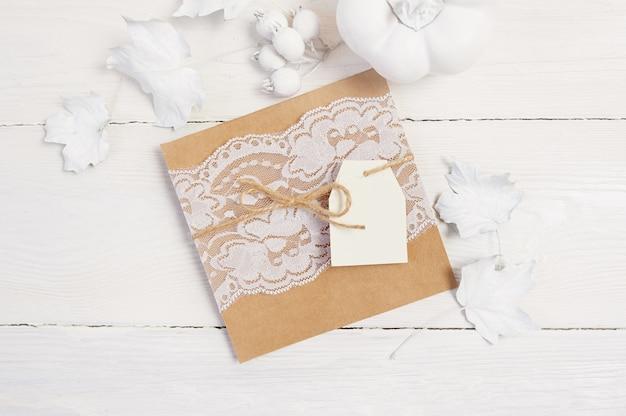 Hoja de papel kraft con etiqueta, calabaza blanca, bayas y hojas sobre madera