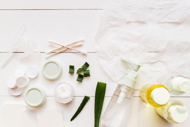 Hoja de papel mascarilla; cotonetes; crema hidratante y aloevera sobre tabla de madera blanca.
