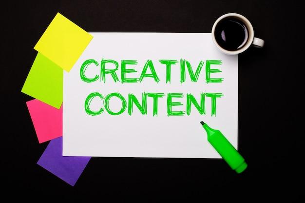 Una hoja de papel con las palabras contenido creativo, una taza de café, pegatinas multicolores brillantes para notas y un marcador verde sobre fondo negro