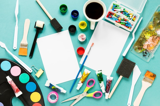 Hoja de papel y paleta de colores de pintura en el escritorio