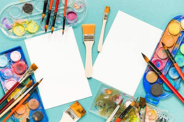 Hoja de papel y paleta de colores de pintura en la mesa