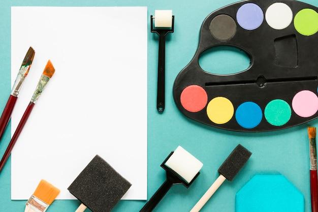 Hoja de papel y paleta de colores de pintura