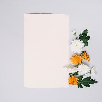 Hoja de papel con pequeñas flores brillantes en mesa