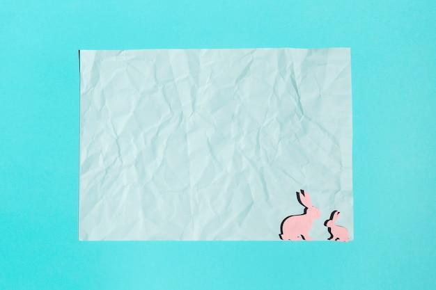 Hoja de papel con pequeños conejos de madera en mesa.