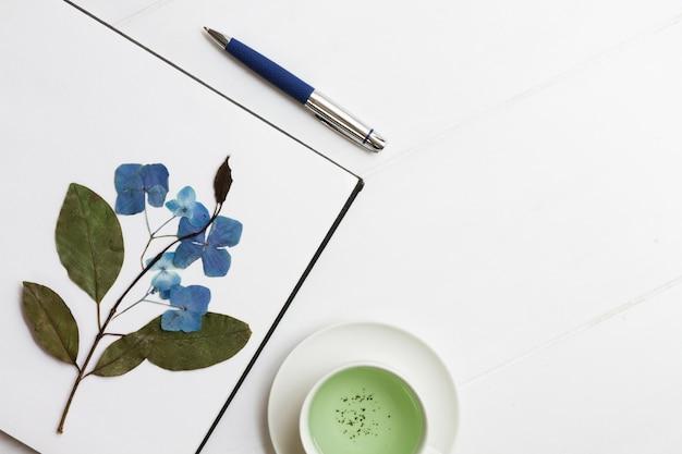 Hoja de papel con rama seca y flores.