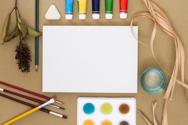 Hoja de papel rodeada de material de dibujo.