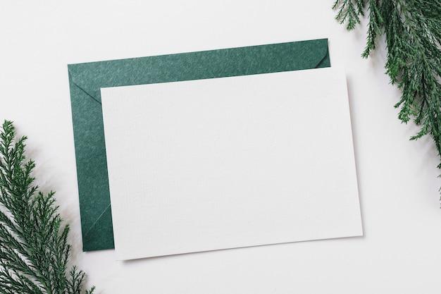 Hoja de papel con sobre verde en mesa