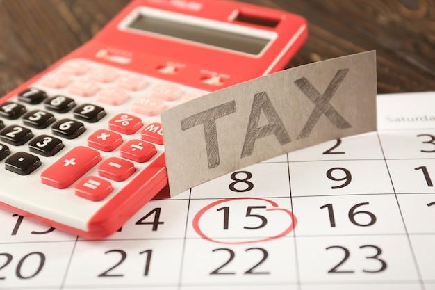Hoja de papel con texto tax y calculadora roja en calendario