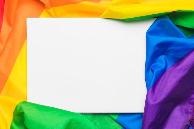Hoja de papel vacía blanca sobre bandera lgbt arrugada