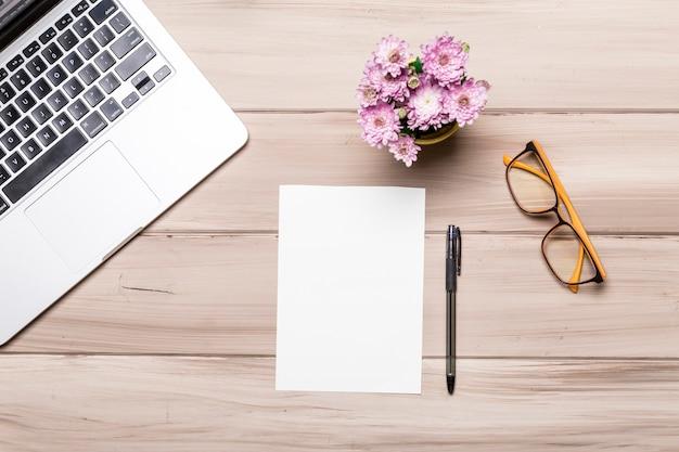 Hoja de papel vacía pluma cuaderno gafas y flores en la mesa