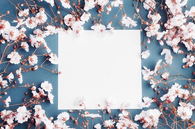 Hoja de papel vacía rodeada de pequeñas flores blancas. tarjeta en blanco sobre fondo azul