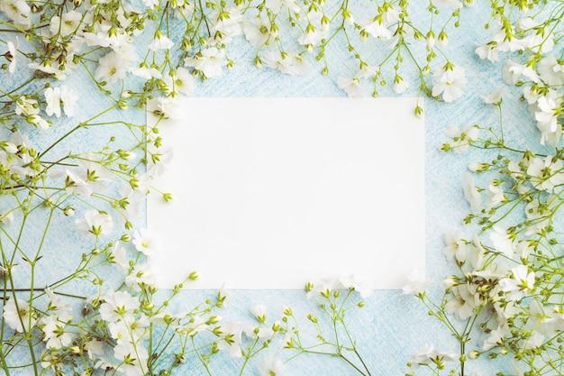 Hoja de papel vacía rodeada de pequeñas flores blancas.