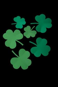 Hoja de papel verde del trébol sobre fondo negro aislado. feliz dia de san patricio.