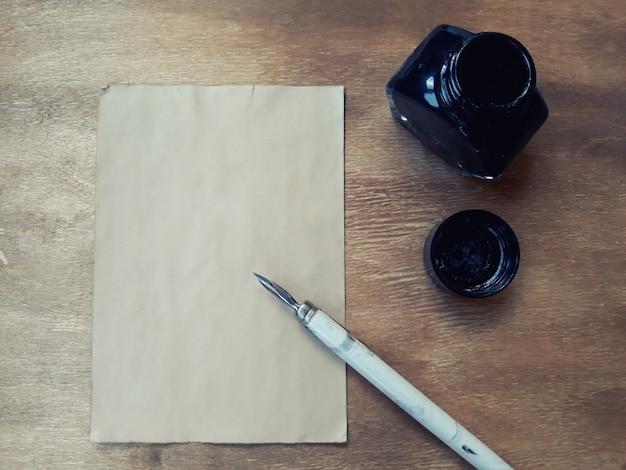 Hoja de papel vieja en blanco con un bolígrafo y un tintero sobre un fondo de madera desgastada, estilo retro