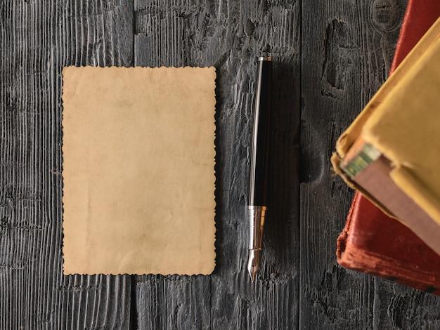 Una hoja de papel viejo y una pluma estilográfica con libros sobre madera.