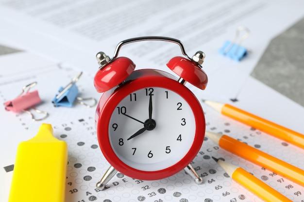 Hoja de puntaje de prueba, reloj despertador y papelería, primer plano