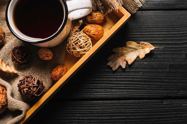 Hoja seca cerca de la bandeja con bebidas y decoraciones