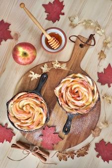Hojaldre casero con rodajas de manzana en forma de rosa al horno en sartenes de hierro sobre madera.