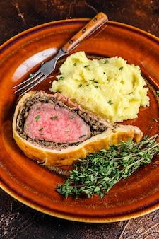 Hojaldre de ternera wellington con puré de patatas en un plato rústico.