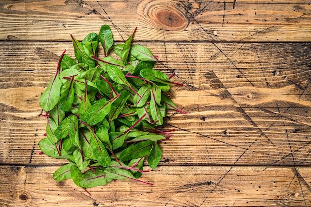Hojas de acelga fresca cruda, mangold, acelga en una mesa de cocina de madera. fondo de madera. vista superior. copie el espacio.