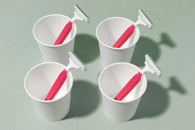 Hojas de afeitar rosa de alta vista en tazas