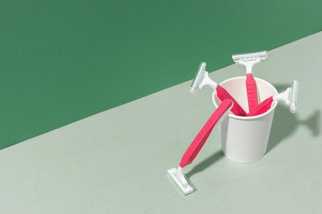 Hojas de afeitar rosa en una taza