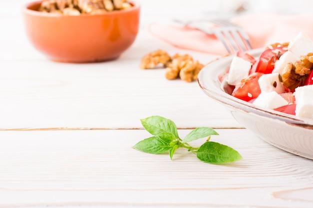 Hojas de albahaca fresca sobre un fondo de ensalada de verduras en un plato sobre una mesa de madera blanca