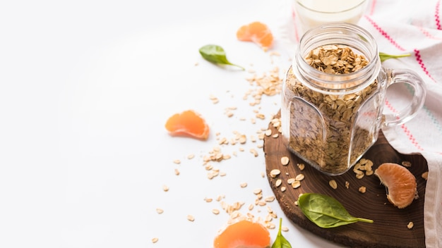 Hojas de albahaca; jarra de avena; rodajas de naranja y servilleta aisladas sobre fondo blanco