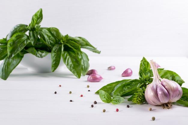 Hojas de albahaca verde fresca con ajo y pimienta sobre superficie blanca