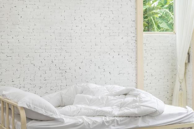 Hojas y almohada blancas del lecho en fondo del sitio blanco.