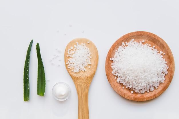 Hojas de aloe vera; crema hidratante de sal de roca y piel sobre fondo blanco