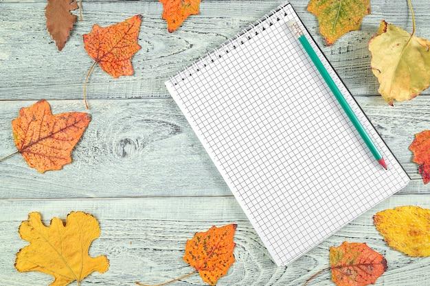 Hojas amarillas de otoño y un cuaderno sobre un fondo claro de madera vieja