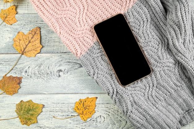 Hojas amarillas de otoño, una taza de té y un teléfono inteligente sobre un fondo de madera vieja