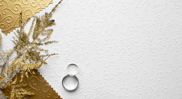 Las hojas y los anillos dorados guardan el concepto de la boda de la fecha